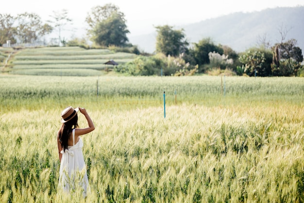 Hermosa mujer disfrutando en campos de cebada.