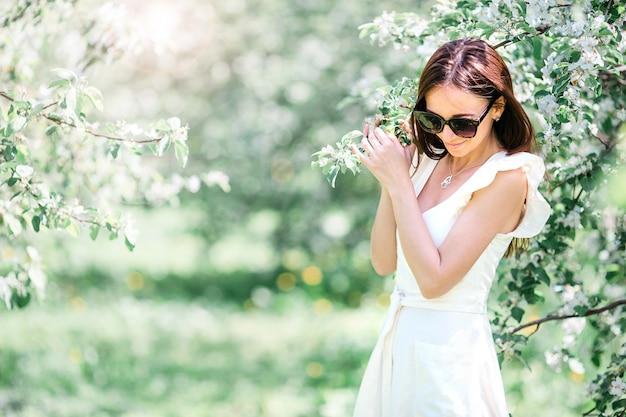 Hermosa mujer disfrutando el olor en el jardín de cerezos de primavera