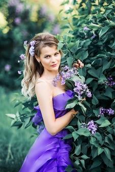 Hermosa mujer disfrutando el olor de la lila. modelo lindo y flores. aromaterapia y concepto de primavera