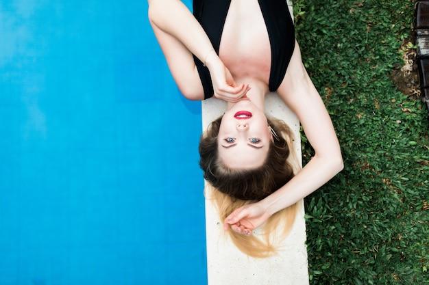 Hermosa mujer divertida sexy brillante se encuentra en el borde de la piscina, tomando el sol, disfruta. cuerpo perfecto y piel y cabello sanos, bikini a la moda, gafas de sol, sandía. vista desde arriba