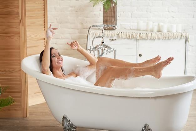 Una hermosa mujer se divierte en una bañera blanca, en una habitación luminosa con una gran ventana.