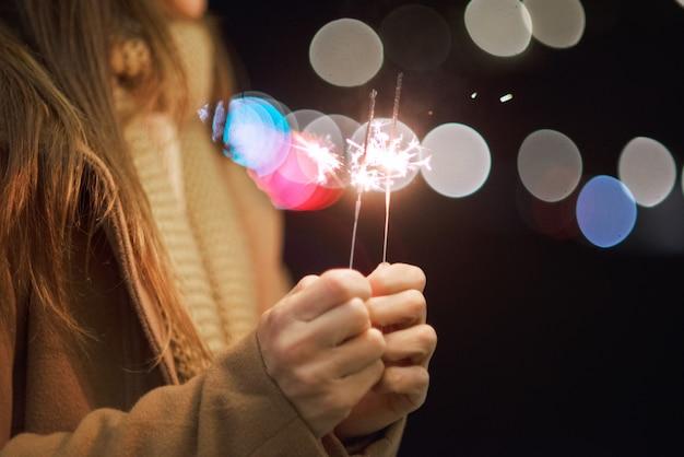 Hermosa mujer divirtiéndose, con bengala en sus manos celebrando la víspera de año nuevo