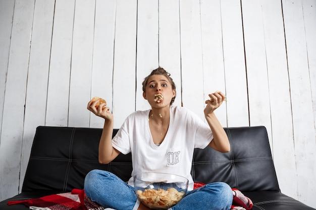 Hermosa mujer doméstica comiendo patatas fritas, viendo la televisión, sentado en el sofá.