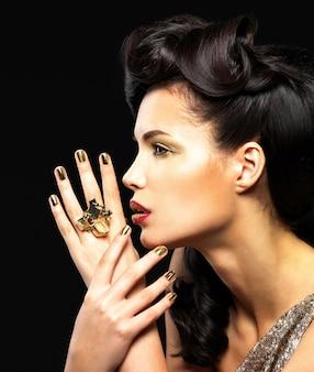 Hermosa mujer con uñas doradas y maquillaje de ojos de moda. modelo de chica morena con peinado estilo en pared negra