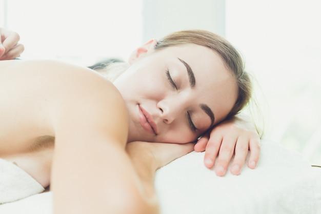 Hermosa mujer durmiendo en la sala de spa, relajarse y cómodo