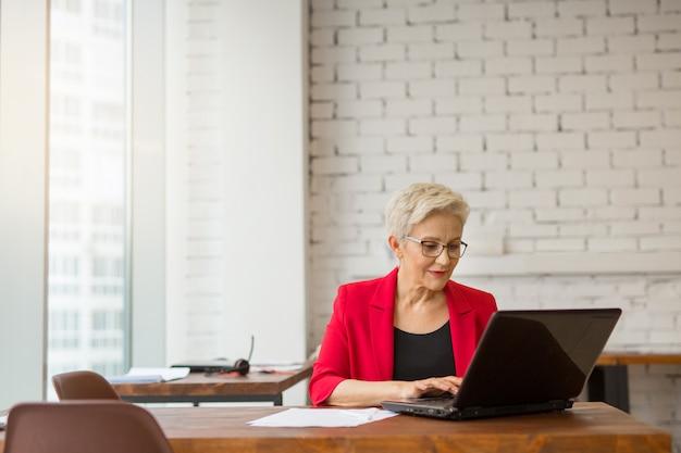 Hermosa mujer de edad en una chaqueta roja trabaja en la oficina con una computadora portátil