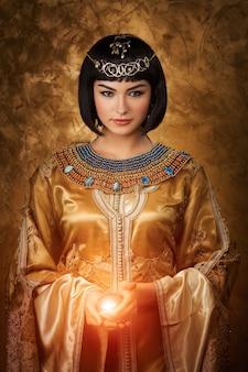 Hermosa mujer egipcia como cleopatra con bola mágica