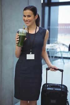 Hermosa mujer ejecutiva de pie con equipaje mientras toma jugo en el pasillo