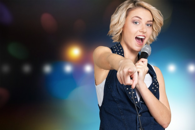 Hermosa mujer elegante cantando karaoke aislado sobre fondo
