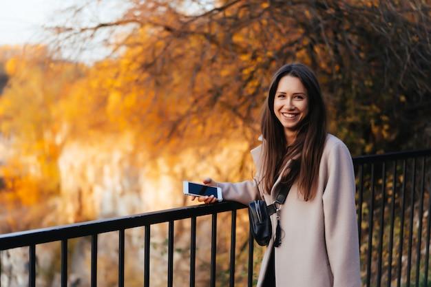 Hermosa mujer elegante de pie en un parque en otoño