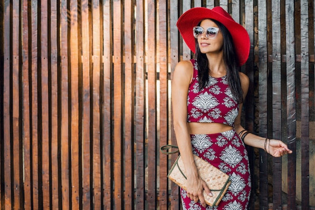 Hermosa mujer elegante posando contra la pared de madera en traje de estilo tropical