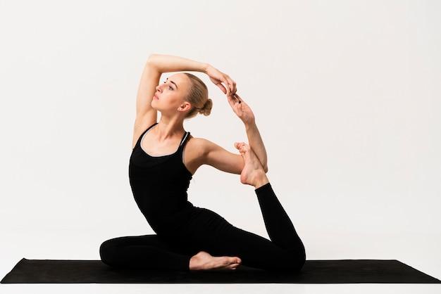 Hermosa mujer elegante posición en clase de yoga