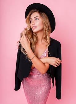 Hermosa mujer elegante con saludable cabello rubio ondulado de pie sobre la pared rosa.