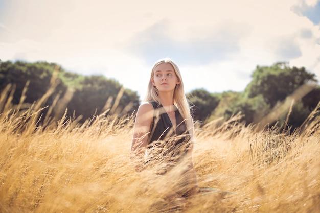 Hermosa mujer elegante sentada en un campo de trigo