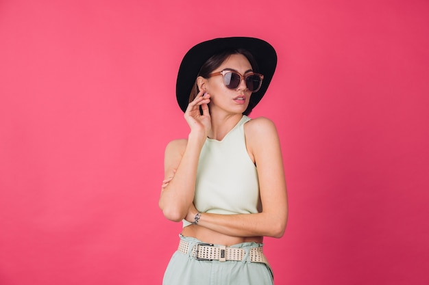 Hermosa mujer elegante con sombrero y gafas de sol posando sobre pared roja rosa