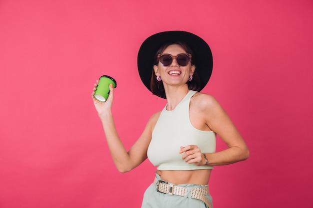 Hermosa mujer elegante con sombrero y gafas de sol posando, sosteniendo una taza de café de papel bailando en movimiento activo feliz emociones positivas,