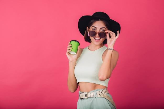 Hermosa mujer elegante con sombrero y gafas de sol posando, sosteniendo una taza de café de papel feliz sonriendo emocionado emociones positivas,