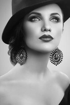 Hermosa mujer elegante con un sombrero posando en el estudio