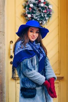 Hermosa mujer elegante con una sonrisa perfecta con sombrero azul y bufanda caminando por la calle. mujer cerca de la puerta amarilla con adornos navideños e inscripción bienvenido.
