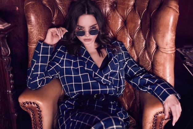 Hermosa mujer elegante en un traje azul sentado en un sillón de cuero