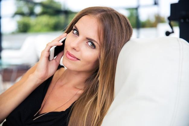 Hermosa mujer elegante en vestido negro hablando por teléfono
