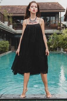 Hermosa mujer en elegante vestido negro largo posando en la piscina de la villa tropical, elegante estilo de verano, vacaciones, tendencia de moda, caminar descalzo