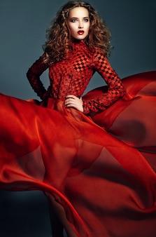 Hermosa mujer elegante en vestido rojo brillante