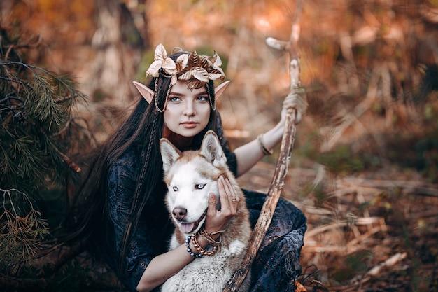 Hermosa mujer elfa, bosque de hadas, corona de corona dorada de cabello largo y oscuro en cabeza con perro rojo