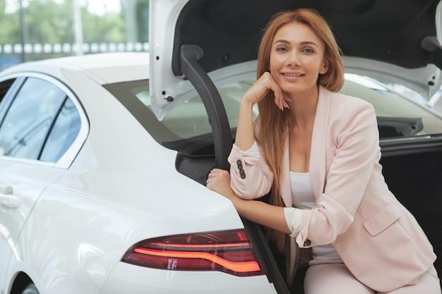 Hermosa mujer eligiendo un auto nuevo en el concesionario