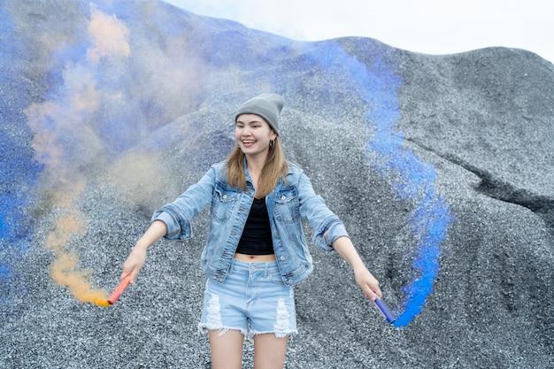 Hermosa mujer ella está jugando un color de humo de fuegos artificiales en el lugar del gran cañón de roca