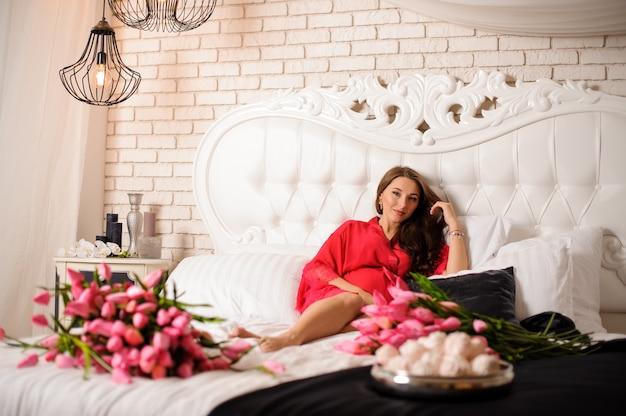 Hermosa mujer embarazada acostada en la cama con un ramo de flores