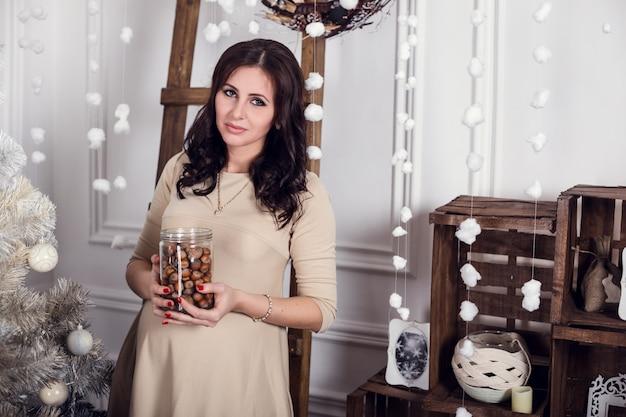 Hermosa mujer embarazada en la casa de invierno con árbol de navidad. , mujer sonriente celebrando navidad o año nuevo. decoración del árbol de navidad. familia