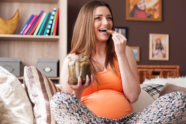 Hermosa mujer embarazada comiendo pepinillos