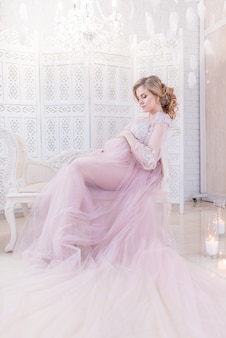 Hermosa mujer embarazada en rico vestido rosa tiene las manos en su vientre posando