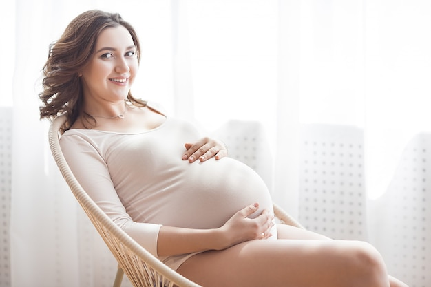 Hermosa mujer embarazada en escena neutral. foto de primer plano expectante.