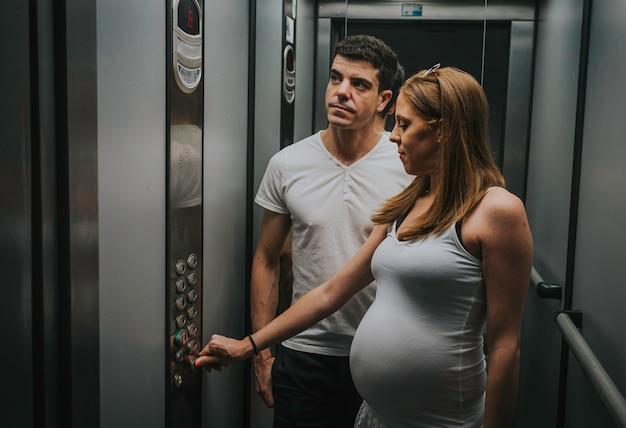 Hermosa mujer embarazada con esposo dentro del elevador