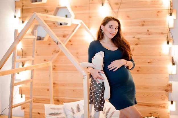 Hermosa mujer embarazada de pelo largo con un juguete entre las luces de guirnaldas