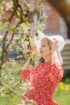 Hermosa mujer embarazada relajándose en el parque con vestido rojo