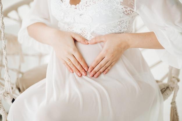Hermosa mujer embarazada rubia sentada en el columpio con flores