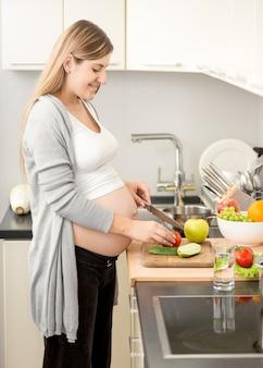 Hermosa mujer embarazada sonriente cocinando la cena en la cocina