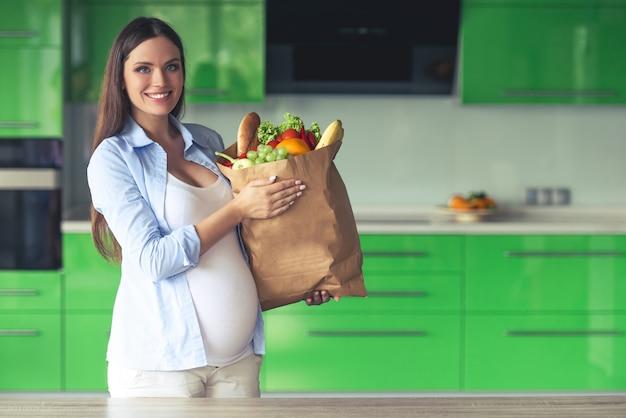 Hermosa mujer embarazada está sosteniendo una bolsa de papel con comida.