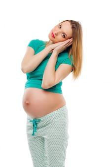 Hermosa mujer embarazada sosteniendo las manos cerca de la cara, como si durmiera. vestido con un pijama brillante. fondo blanco aislado