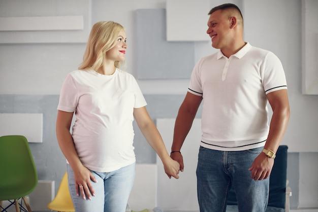 Hermosa mujer embarazada con su esposo en un estudio