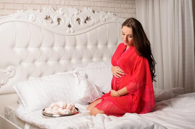 Hermosa mujer embarazada vestida con elegante bata sentada en la cama