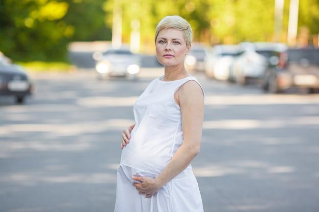 Hermosa mujer embarazada en vestido blanco abraza el vientre