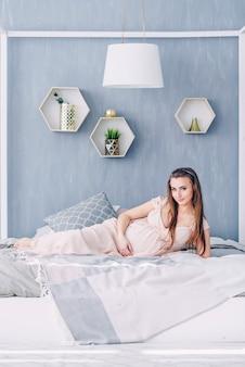 Hermosa mujer embarazada en un vestido rosa se encuentra en una cama