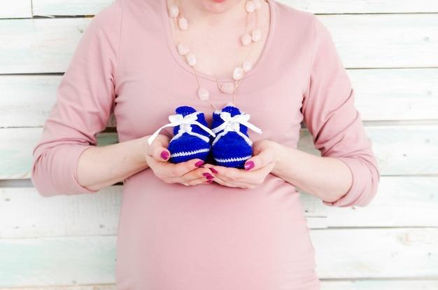 Hermosa mujer embarazada en un vestido rosa