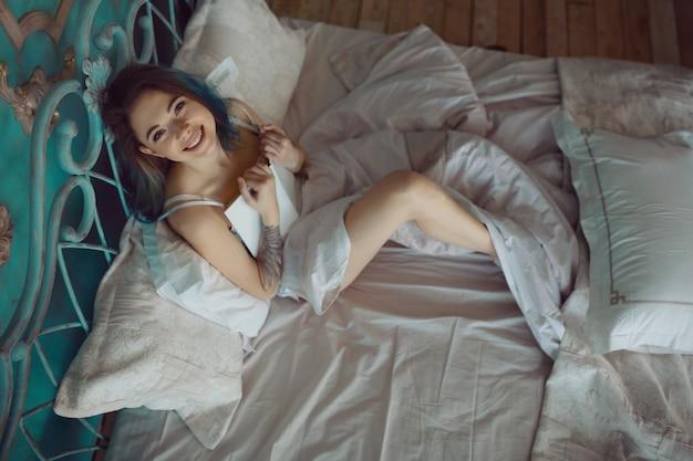 Hermosa mujer emocionada sonriente leyendo un libro en la mañana