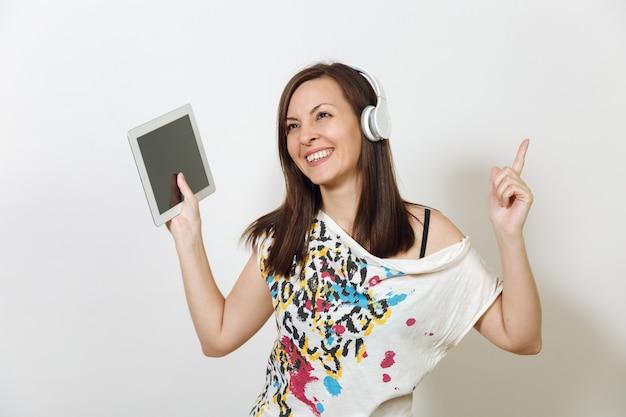 La hermosa mujer emocional europea de cabello castaño con piel sana y limpia, sonrisa encantadora, vestida con ropa ligera casual, escucha y disfruta de la música en auriculares con tableta sobre un fondo blanco.