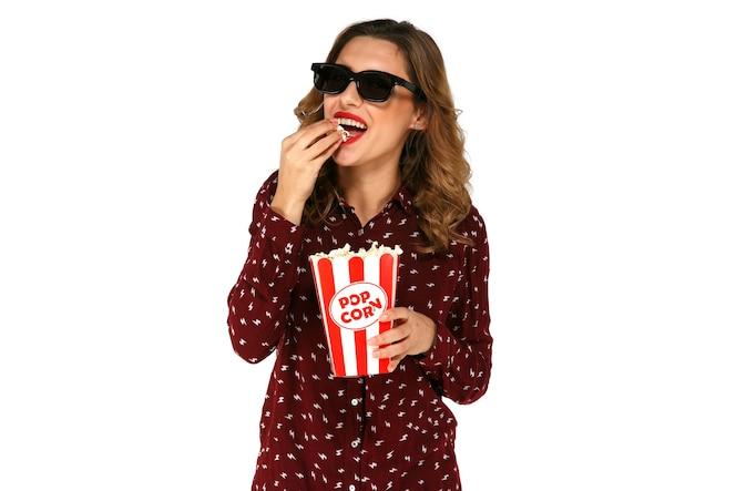 Hermosa mujer en gafas 3d comiendo palomitas de maíz con palomitas de maíz